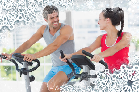 Smiling couple working out at spinning class against snow photo