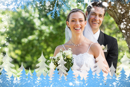 Newly wed couple with flower bouquet in park against snow photo