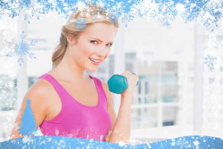 Pretty blonde lifting dumbbells and smiling at camera against snow photo