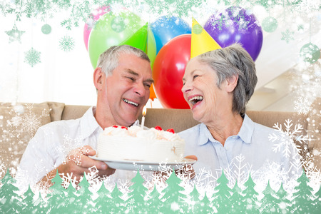 Senior couple sitting on couch celebrating a birthday against snow photo