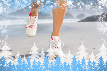 Composite image of fit woman walking on the beach against snow photo