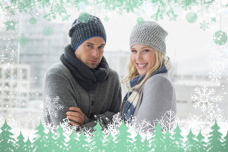 Cute couple in warm clothing smiling at camera against snow photo