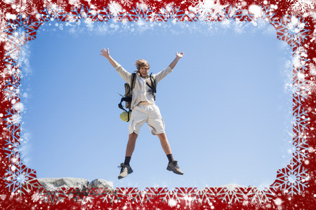 Handsome hiker jumping at the summit smiling at camera against snow photo