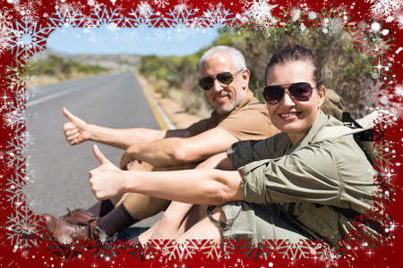 Hitch hiking couple sitting on the side of the road smiling at camera against snow photo