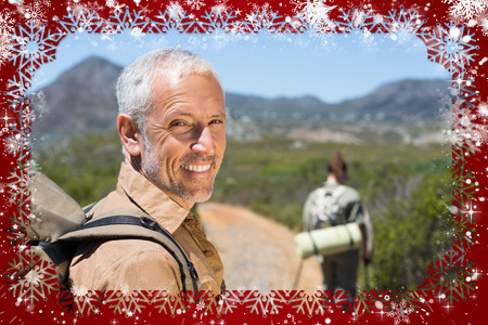 Hiking couple walking on mountain trail man smiling at camera against snow photo