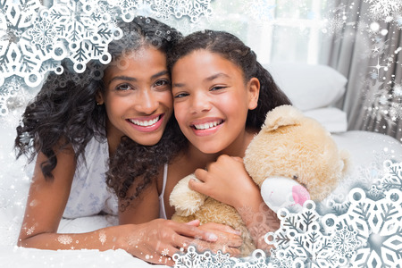 Pretty woman lying on bed with her daughter smiling at camera against snow photo