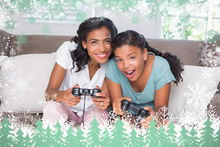 Happy mother and daughter playing video games together on sofa against snow photo