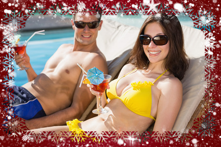 Smiling couple with drinks sitting by swimming pool against snow photo