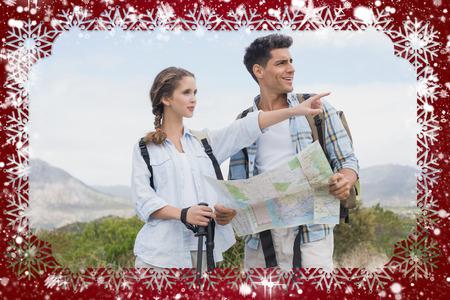 Hiking couple with map pointing ahead on mountain terrain against snow photo