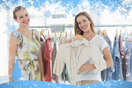 Composite image of young women shopping in clothes store against snow photo