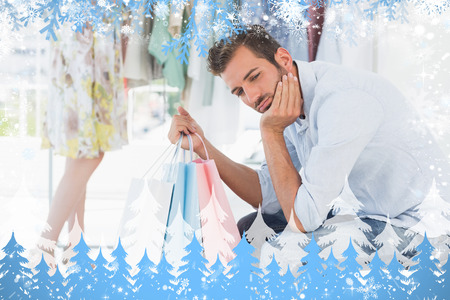 boring frame: Bored man with shopping bags while woman by clothes rack against snow Stock Photo