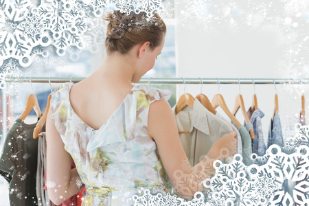 Female customer selecting clothes at clothing rack in store against snow photo