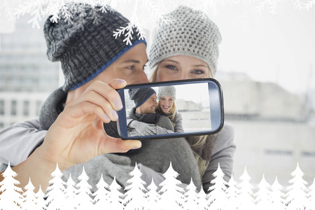 Hand holding smartphone showing photo against fir tree forest and snowflakes photo