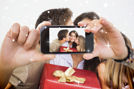 Hand holding smartphone showing photo against snow photo