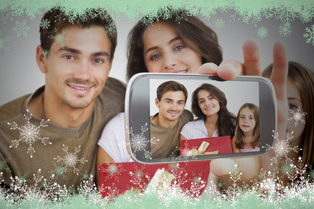 Hand holding smartphone showing photo against snow flake frame in green photo