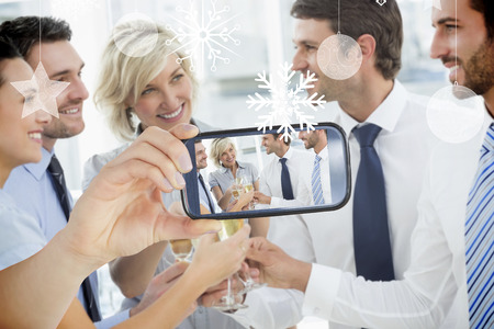 Hand holding smartphone showing photo against hanging decorations photo