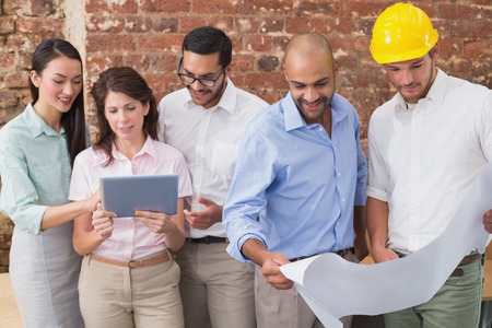Architect colleagues working on blueprints and digital tablet at office photo