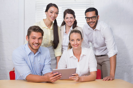 Smiling business people using digital tablet in meeting at the office photo