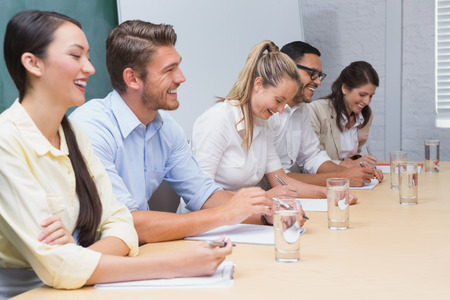 Smiling business people taking notes at a presentation in the office photo