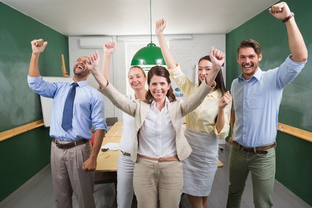 Excited business team cheering at camera in the office photo