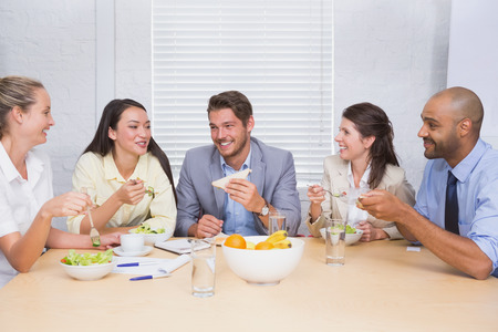 Workers laughing while enjoying lunch break in the office photo