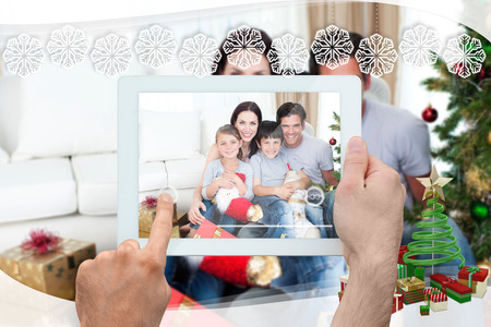 Hand holding tablet pc against snowflake frame photo