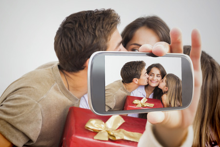 Composite image of hand holding smartphone showing photograph photo