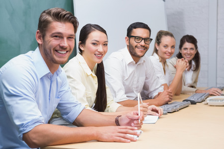 Smiling business team sitting in a line in the office photo