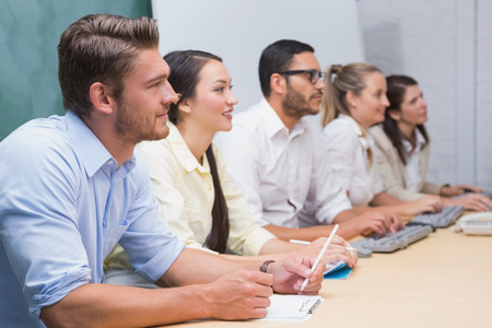 Business team sitting in a line listening during a meeting in the office photo