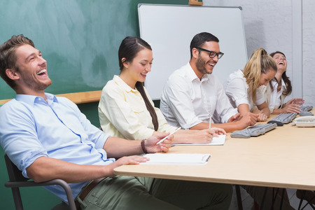 Casual business team laughing during meeting in the office photo