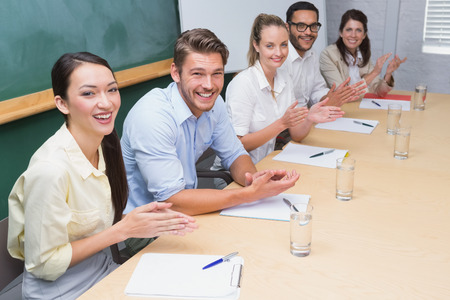 Business team sitting in a row clapping at camera in the office photo