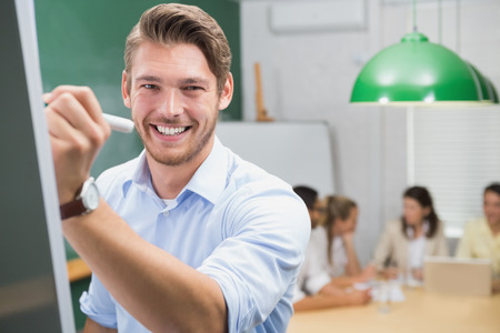 Smiling businessman writing on whiteboard with marker in the office photo