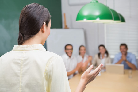 Smiling businesswoman giving presentation to her colleagues in the office photo