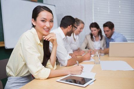 Businesswoman smiling at camera with team behind her in the office photo