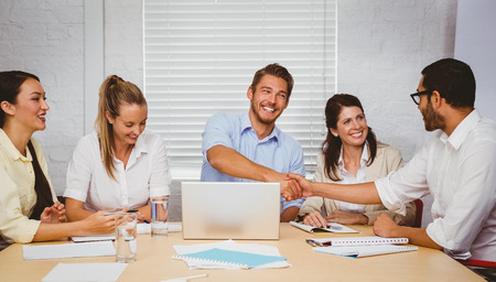 casual business: Casual business people shaking hands at desk and smiling in the office