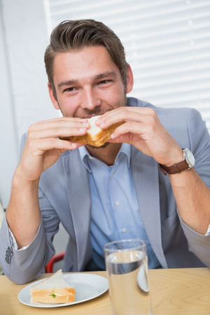 lunch hour: Smiling businessman eating a sandwich during the lunch hour at work