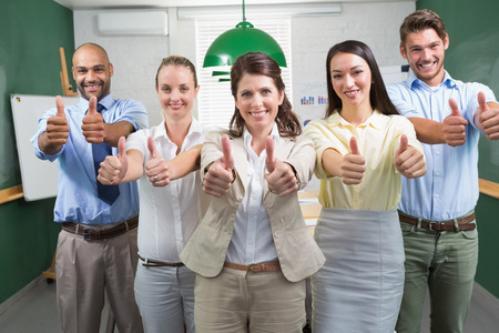 Business team looking at camera and giving thumbs up in the office photo