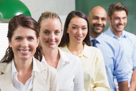Business team standing in a row smiling at camera in the office photo