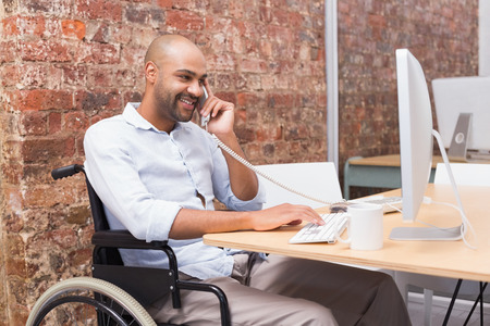 wheelchair man: Businessman in wheelchair working at his desk on the phone in the office