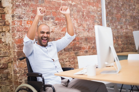 Casual businessman in wheelchair cheering at his desk in the office photo