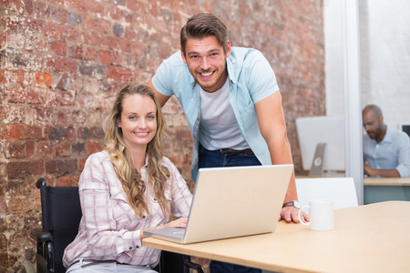 Smiling businesswoman in wheelchair working with colleague in the office photo