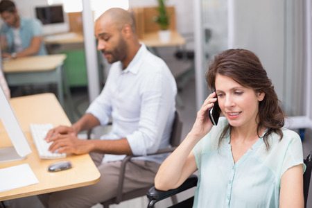 Smiling businesswoman in wheelchair on the phone in front of his colleague in the office photo