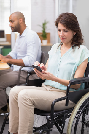 Businesswoman in wheelchair texting on phone in the office photo