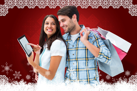 Happy couple with shopping bags against christmas themed snow flake frame photo