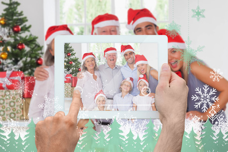 Hand holding tablet pc against snowflakes and fir trees in green photo