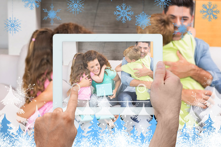 Hand holding tablet pc against snowflakes and fir trees photo