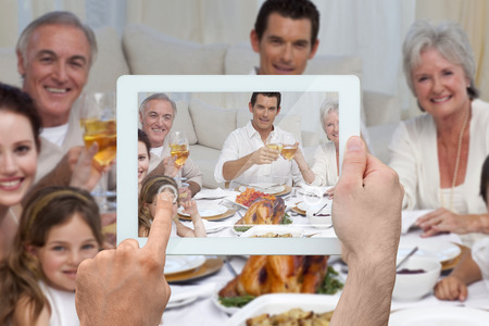 thanksgiving adult: Composite image of hand holding tablet pc showing photograph