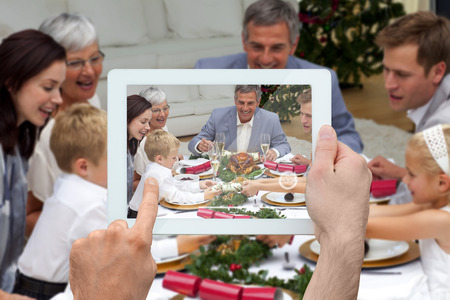 Composite image of hand holding tablet pc showing photograph photo