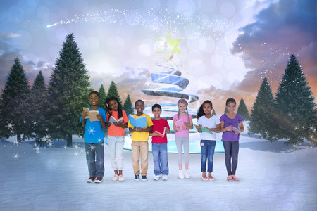 Composite image of cute children against snowy landscape with fir trees photo