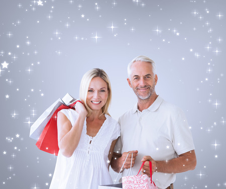 Composite image of happy couple with shopping bags against grey vignette photo